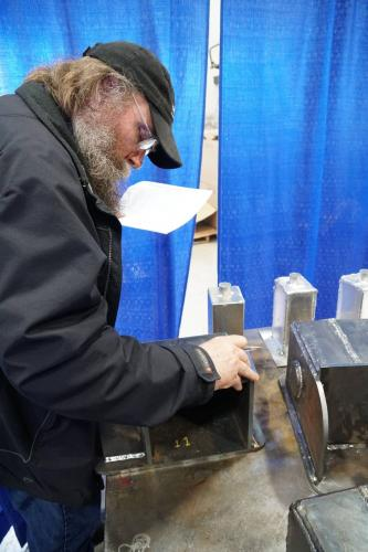 Brad Moe, Welding Quality Control Technician with Seaspan inspect the welds on parts supplied by Brenco.